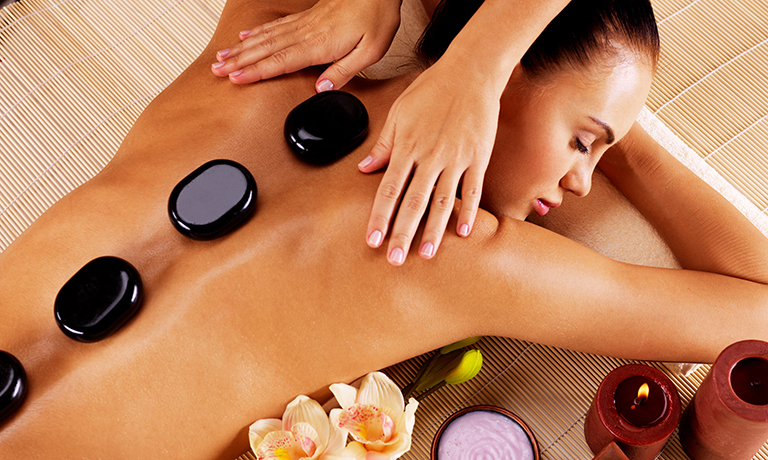Adult woman having hot stone massage in spa salon. Beauty treatm